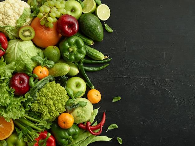 Prato de comida saudável em fundo de pedra preta. conjunto saudável, incluindo vegetais e frutas. uva, maçã, kiwi, pimenta, limão, repolho, abobrinha, toranja. nutrição adequada ou menu vegetariano.