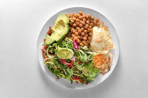 Prato de comida saudável filé de frango, salada, abacate e mingau de arroz integral. em uma placa branca em um suporte de ardósia preta.
