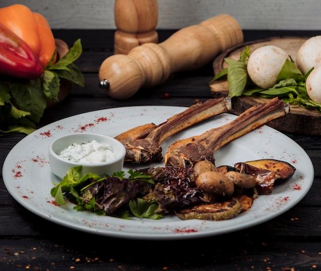 Prato de costela de cordeiro kebab servido com iogurte, salada e legumes grelhados