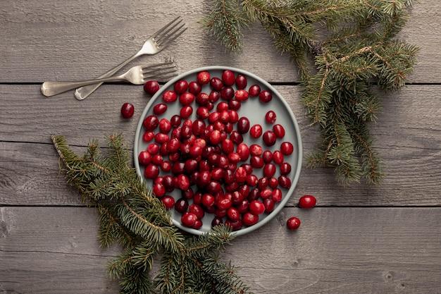 Prato de cranberries com pinheiros e garfos