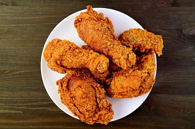 Prato de deliciosas galinhas fritas, douradas e crocantes, na superfície de madeira