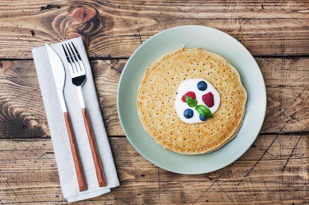 Prato de deliciosas panquecas finas com frutas na mesa de madeira