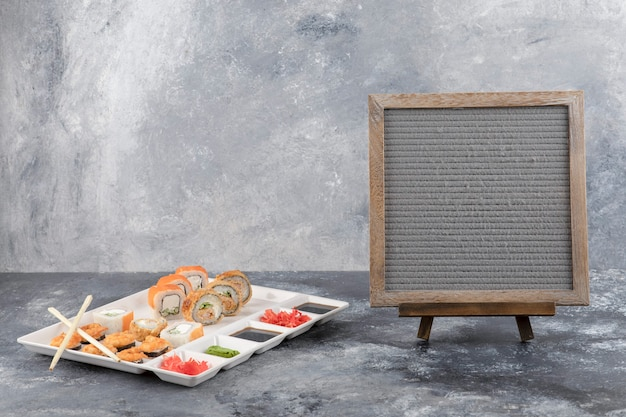 Prato de deliciosos rolos de sushi e moldura de madeira com fundo de mármore