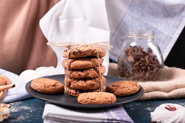 Prato de doces e dois bolos e biscoitos com canela