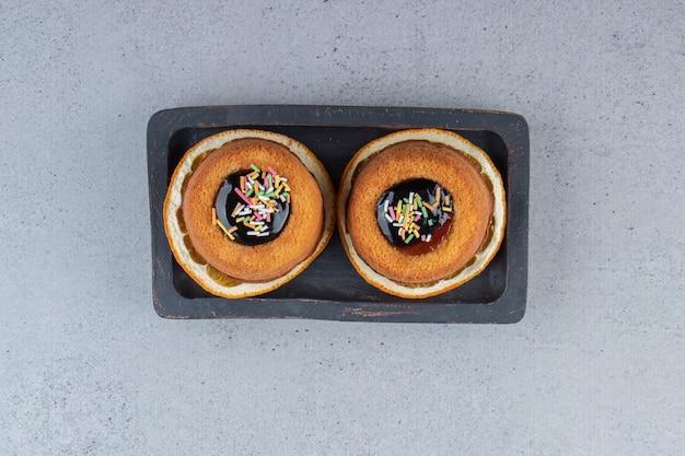 Prato de dois mini-bolos com geleia colocado em cima da rodela de laranja. foto de alta qualidade
