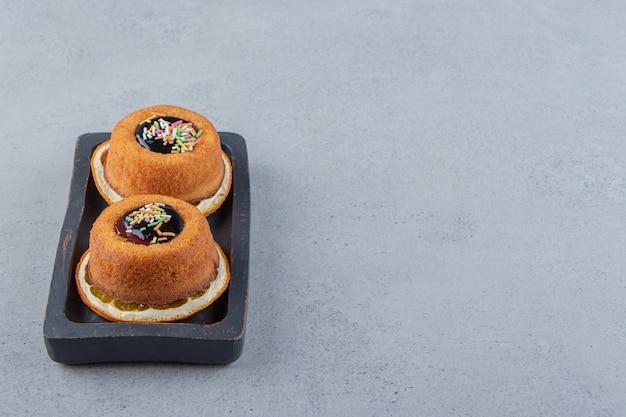 Prato de dois minibolos com geleia colocado em cima de uma rodela de laranja