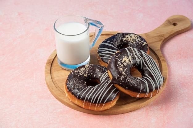 Prato de donuts de chocolate com um copo de leite na superfície rosa.
