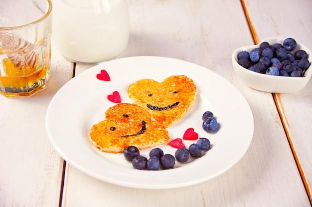 Prato de duas panquecas em forma de coração com bagas na mesa branca