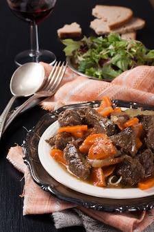 Prato de ensopado de carne com salada verde