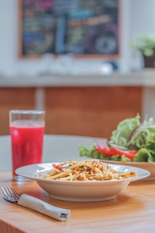 Prato de espaguete com legumes wok e salada fresca em um restaurante. fechar-se.