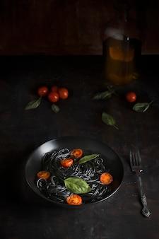 Prato de espaguete preto, com tomate cereja e manjericão, sobre um fundo preto de madeira