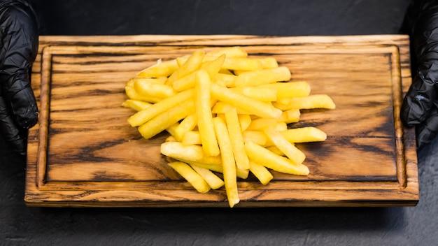 Prato de fast food. vista superior de batatas fritas salgadas na placa de madeira rústica nas mãos do chef.