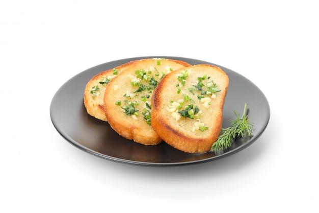 Prato de fatias de pão torrado com alho isolado no branco