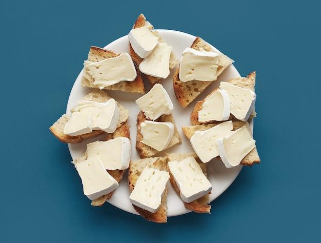 Prato de fatias de pão torrado com queijo brie fresco no fundo azul, vista superior