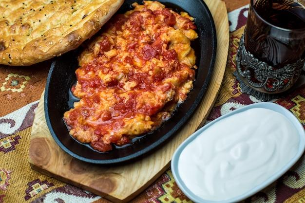 Prato de ferro fundido com ovo e tomate, servido com iogurte e pão tandoor