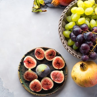Prato de figos roxos, uvas e romã