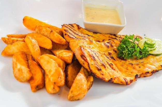 Prato de filé de frango assado com batata frita e molho