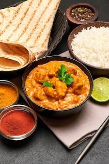 Prato de frango ao curry tradicional e arroz na mesa escura