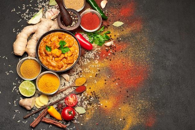 Prato de frango ao curry tradicional e temperos na mesa escura