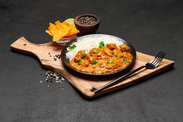 Prato de frango com curry tradicional, arroz e especiarias na mesa escura