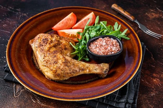 Prato de frango - coxas de frango assadas com salada de vegetais. fundo escuro. vista do topo.