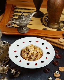 Prato de frango fettuccini servido ao lado de gamão