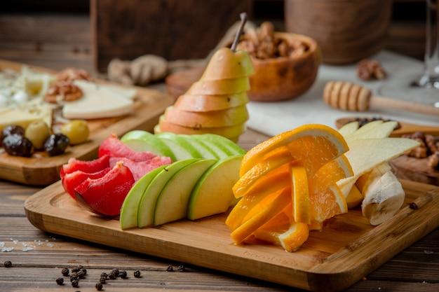 Prato de frutas com fatias de maçã, banana, ameixa e laranja