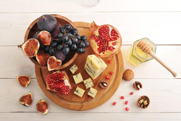 Prato de frutas com figos, uvas, romã e queijo com mel na superfície de madeira