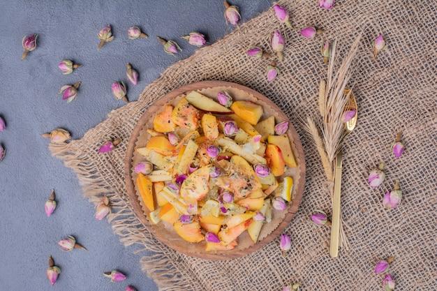 Prato de frutas fatiadas com flores e pano azul.