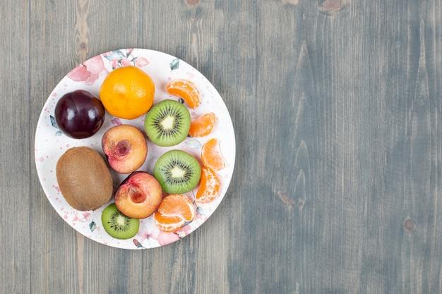 Prato de frutas fatiadas em superfície de madeira