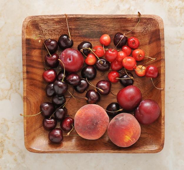Prato de frutas - pêssegos, ameixas, cerejas no prato de madeira.