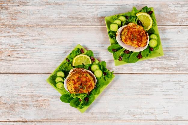 Prato de frutos do mar com amêijoas recheadas com fundo de madeira.