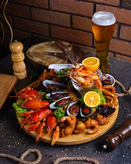 Prato de frutos do mar com camarões, mexilhões, lagostas servidas com limão e copo de cerveja