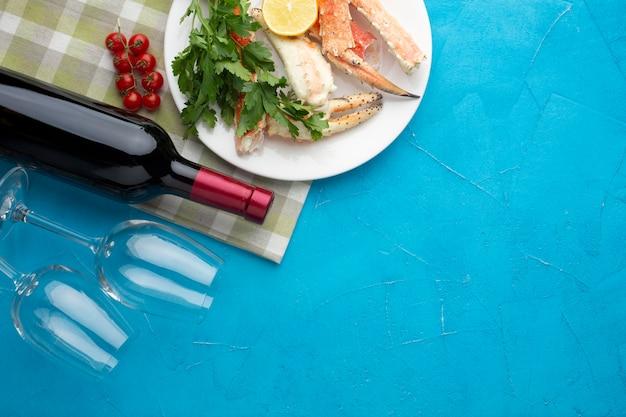 Prato de frutos do mar com garrafa de vinho e copos