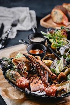 Prato de frutos do mar grelhado. marisco grelhado delicioso sortido com legumes. bastardos misturados grelhados com molho de pimenta e legumes. fundo azul
