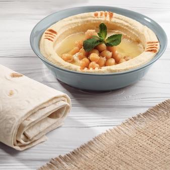 Prato de homus com pão na mesa de madeira e hessian