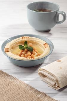 Prato de hummus árabe café da manhã com pão e uma xícara de chá de menta quente na mesa de madeira branca