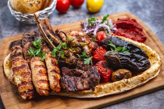 Prato de kebab com lula de cordeiro e frango e tikka kebabs legumes grelhados com salada de cebola roxa