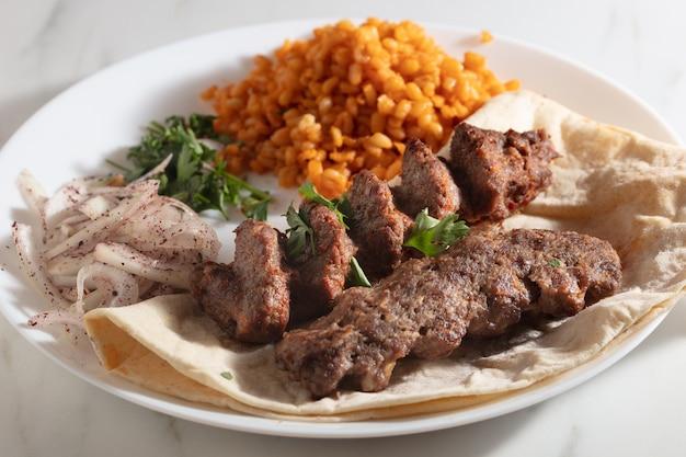 Prato de kebab com pão e cebola e um pouco de arroz temperado