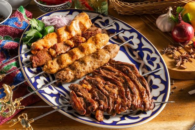 Prato de kebabs. uch-panzha de cordeiro, kebab de frango kebab com cordeiro, shish kebab de frango e espetos de cordeiro em um prato com enfeite tradicional do uzbequistão.