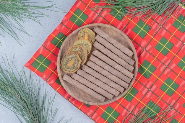 Prato de kiwi seco e biscoitos na toalha de mesa colorida.