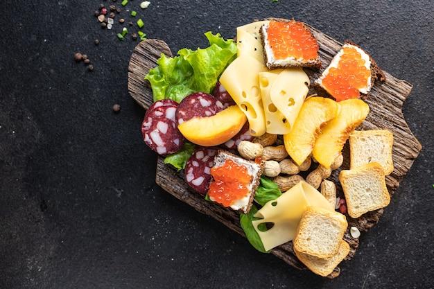 Prato de lanche, antepasto caviar, salsicha, carne, queijo, nozes, pêssego, torrada, pão, aperitivos