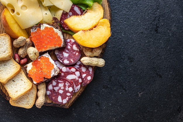 Prato de lanche, antepasto caviar, salsicha, carne, queijo, nozes, pêssego, torrada, pão, aperitivos Foto Premium