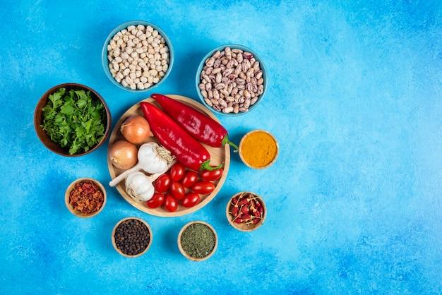 Prato de legumes, feijão e especiarias sobre fundo azul.