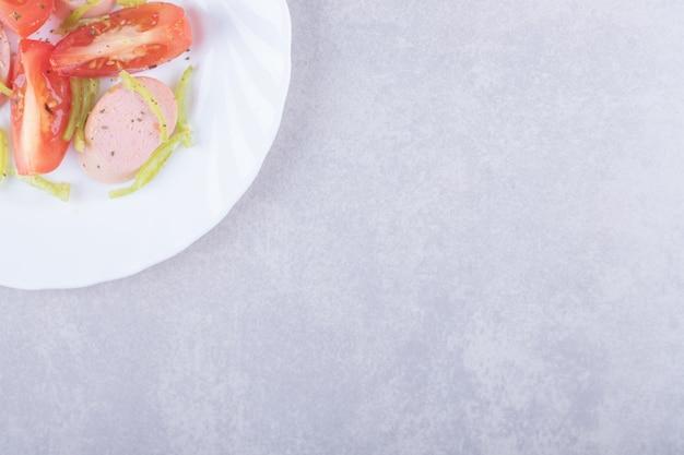 Prato de linguiças fatiadas e tomates em fundo de pedra.