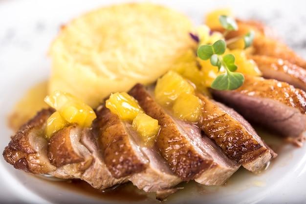 Prato de luxo com fatias de peito de pato, pedaços de abacaxi, molho doce, purê de batata