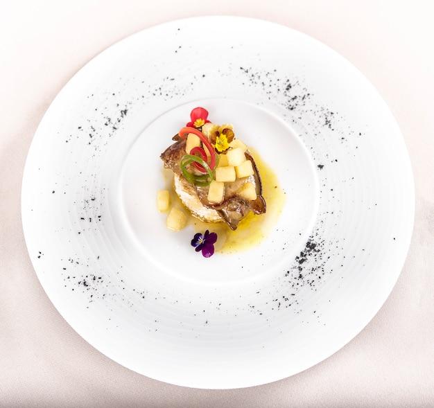 Prato de luxo com fígado de pato, abacaxi e pedaços de manga, molho doce, colocado no torrado