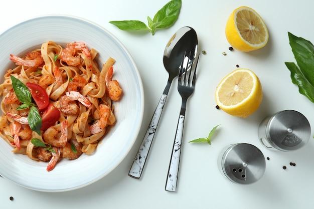 Prato de macarrão de camarão e ingredientes em fundo branco