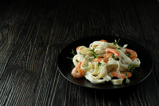Prato de macarrão de camarão em fundo de madeira rústico