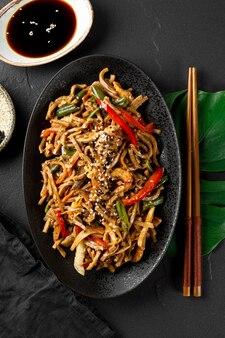 Prato de macarrão de trigo sarraceno asiático soba com legumes, cogumelos e frango em fundo escuro fechar